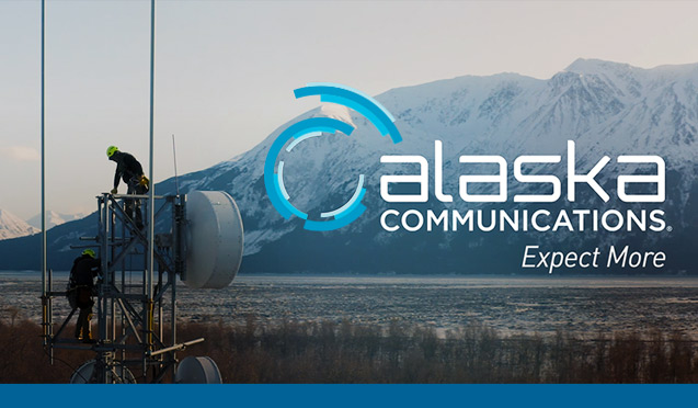 Communications workers atop a tower overlooking Turnagain Arm with the snow-capped Kenai Mountains in the distance